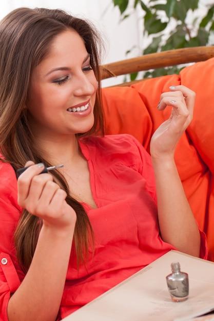 Mulher faz manicure em casa Foto gratuita