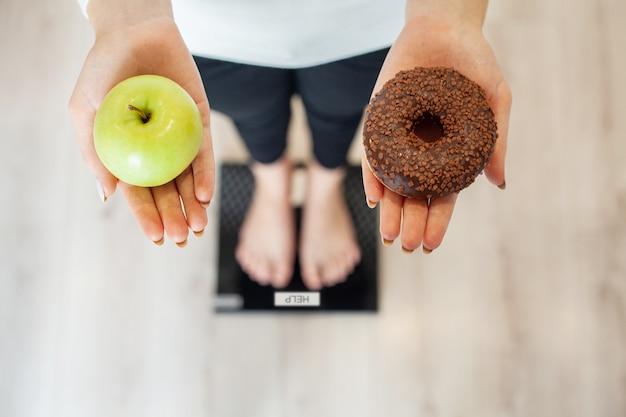 Mulher faz uma escolha entre alimentos saudáveis e prejudiciais Foto Premium