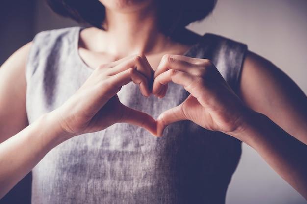 Mulher fazendo as mãos em forma de coração, seguro de saúde do coração Foto Premium