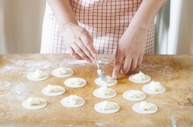 Mulher fazendo bolinhos de massa, vareniks. feito à mão. Foto Premium