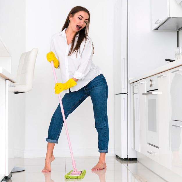 Mulher fazendo caretas durante a limpeza Foto gratuita