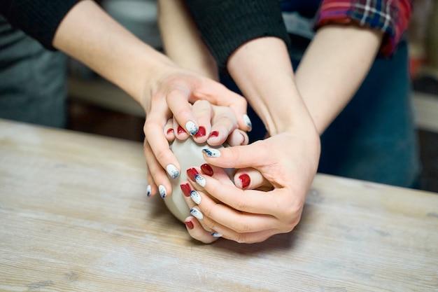 Mulher fazendo cerâmica, close-up de quatro mãos, foco em oleiros, palmas das mãos com cerâmica Foto Premium