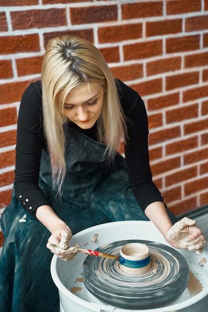 Mulher fazendo cerâmica na roda, pinta azul. conceito de mulher em freelance, negócios Foto Premium