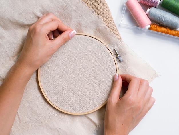 Mulher fazendo decorações com anéis de madeira e tecido Foto gratuita