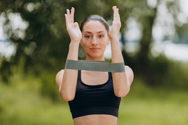 Mulher fazendo exercício para as mãos com uma fita no parque ao ar livre. Foto Premium