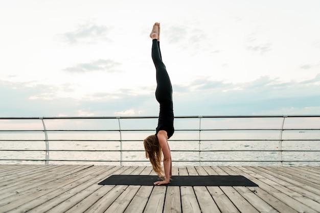 Mulher, fazendo, ioga, e, ficar, ligado, dela, mãos, perto, a, mar, de manhã Foto Premium