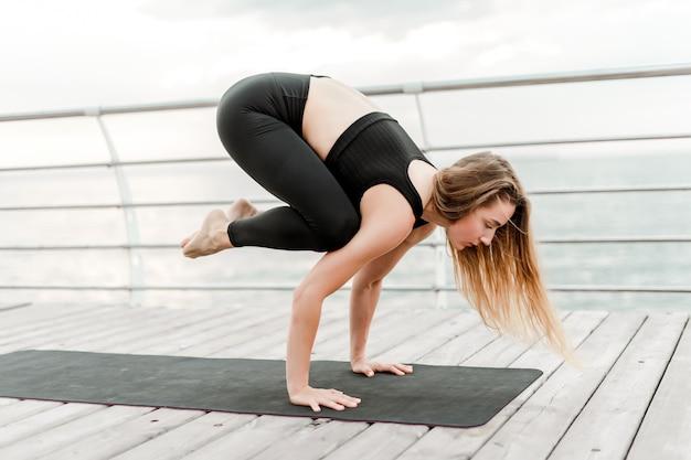 Mulher, fazendo, ioga, praia, e, ficar, dela, mãos Foto Premium