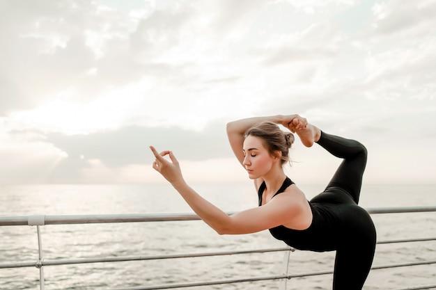 Mulher, fazendo, ioga, praia, em, difícil, asana, posição Foto Premium