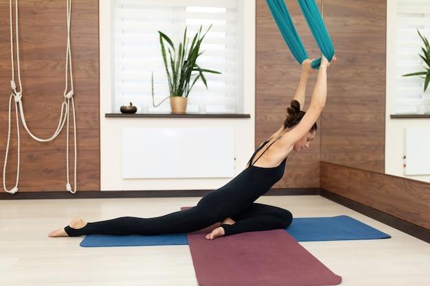 Mulher fazendo ioga voar esticando exercícios no ginásio. estilo de vida apto e bem-estar Foto Premium