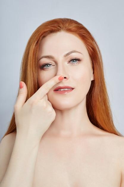 Mulher fazendo massagem facial, ginástica, linhas de massagem e olhos e nariz de boca de plástico Foto Premium
