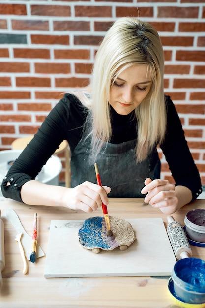 Mulher fazendo padrão na placa cerâmica com pincel. conceito de passatempo criativo. Foto Premium