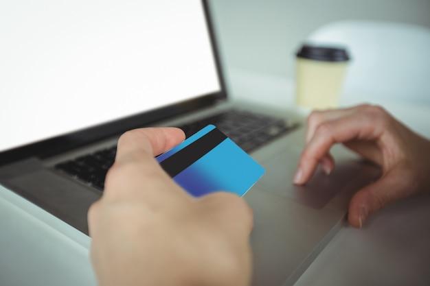Mulher fazendo pagamento on-line usando o laptop e cartão de crédito Foto gratuita