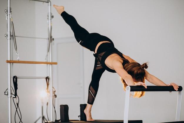 Mulher fazendo pilates em um reformador Foto gratuita
