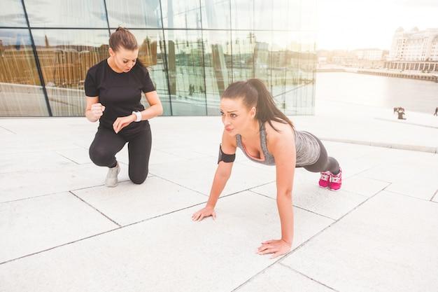 Mulher, fazendo, push-ups, exercícios, com, dela, treinador pessoal Foto Premium