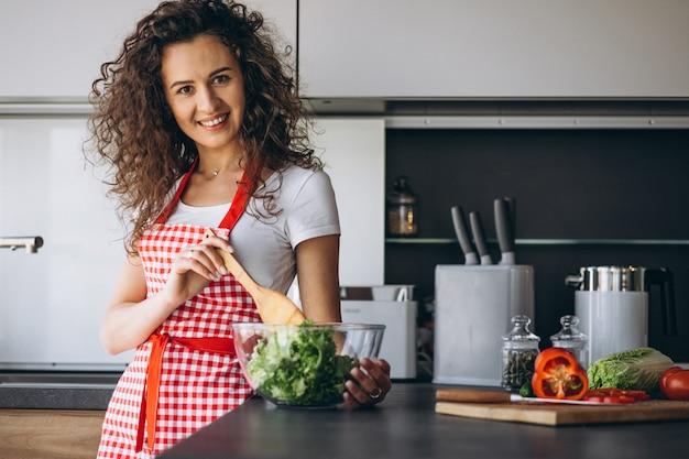 Mulher fazendo salada na cozinha Foto gratuita