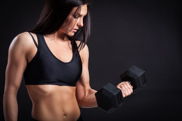 Mulher fazendo um exercício com um haltere Foto Premium