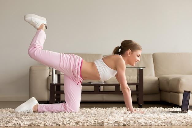 Mulher fazendo um exercício de kickback do joelho em casa Foto gratuita