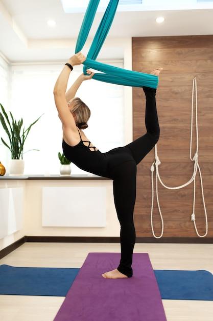 Mulher fazendo yoga com mosca, esticando o pé em uma perna no chão e a segunda na rede Foto Premium