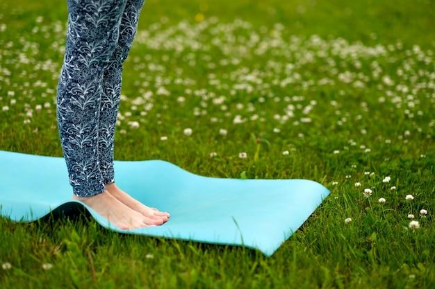 Mulher fazendo yoga na grama verde Foto Premium