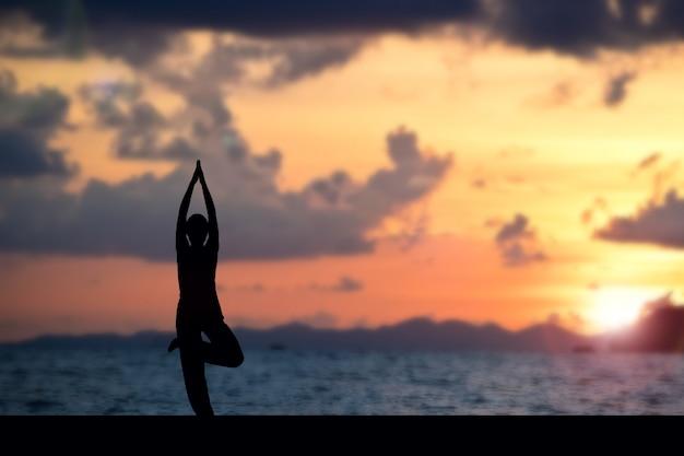 Mulher fazendo yoga na praia Foto Premium