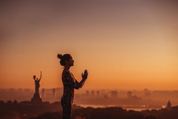 Mulher fazendo yoga no telhado de um arranha-céu na cidade grande. Foto gratuita