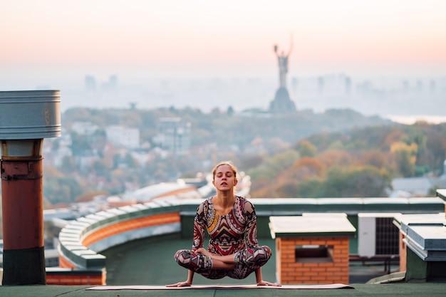 Mulher fazendo yoga no telhado de um arranha-céu na cidade grande Foto gratuita