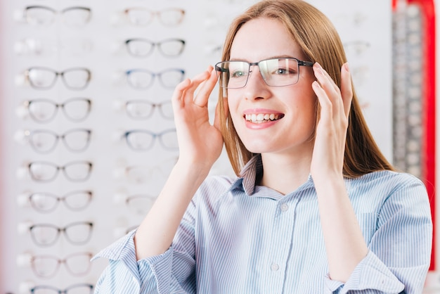 Mulher feliz à procura de novos óculos no optometrista Foto gratuita