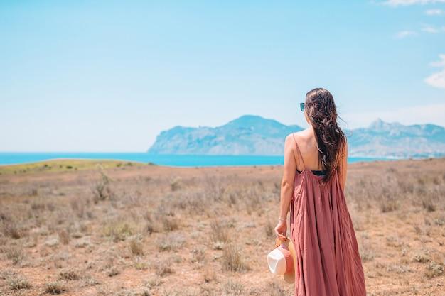 Mulher feliz ao ar livre na beira do penhasco apreciar a vista sobre a rocha no topo da montanha Foto Premium
