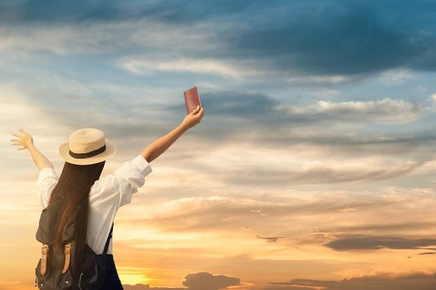 Mulher feliz aparecer passaporte com pôr do sol. Foto Premium