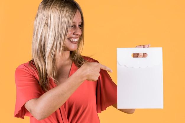 Mulher feliz, apontando para o saco de papel branco em fundo colorido Foto gratuita