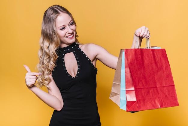 Mulher feliz, apontando para sacos de papel Foto gratuita