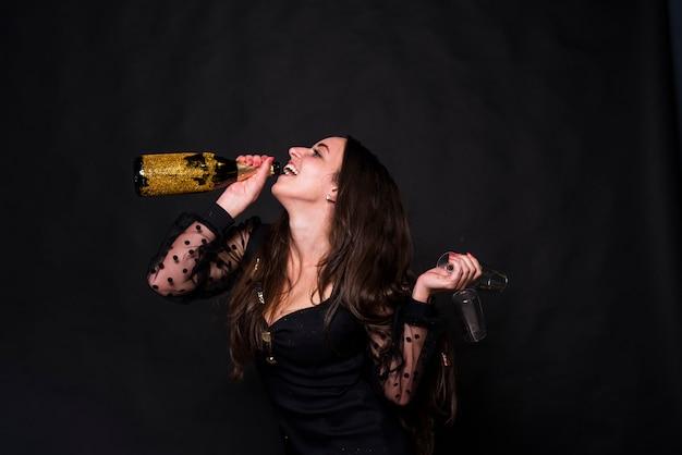 Mulher feliz, bebendo, champanhe, de, garrafa Foto gratuita