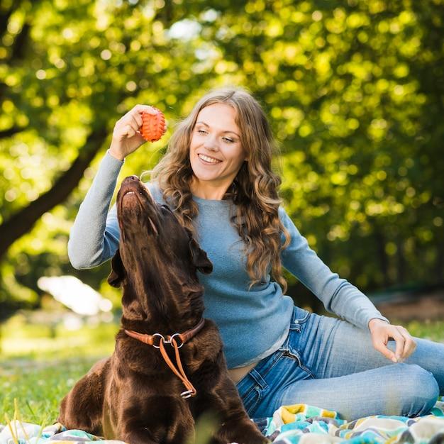 Mulher feliz brincando com seu cachorro no jardim Foto gratuita