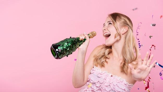 Mulher feliz cantando na garrafa de champanhe Foto gratuita