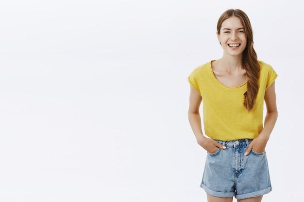 Mulher feliz, charmosa e simpática, com cabelo trançado, posando de camiseta amarela e shorts, sorrindo encantada e segurando as mãos nos bolsos, em pé casualmente Foto gratuita