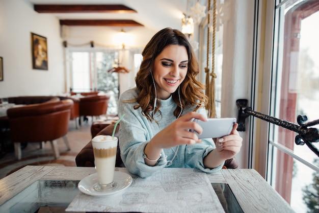 Mulher feliz com cachos no café usando telefone inteligente e sorrindo Foto gratuita