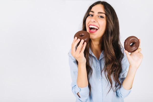 Mulher feliz, com, dois, donuts Foto gratuita