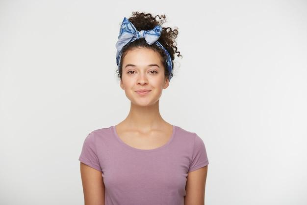 Mulher feliz com expressão positiva, vestida com camiseta casual e tiara estilosa Foto gratuita
