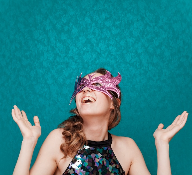 Mulher feliz com máscara rosa ri Foto gratuita
