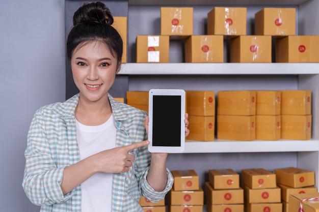 Mulher feliz com seu tablet digital e caixa de encomendas de correio no escritório em casa Foto Premium