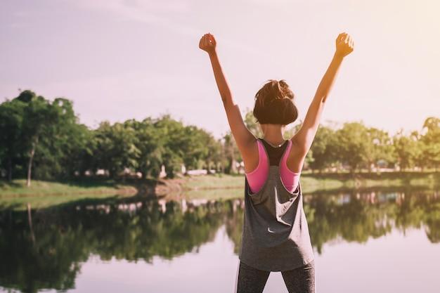 Mulher feliz com show de mão e em pé sobre o rio Foto Premium