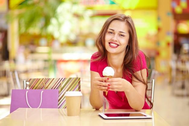 Mulher feliz com um sorvete e café Foto gratuita
