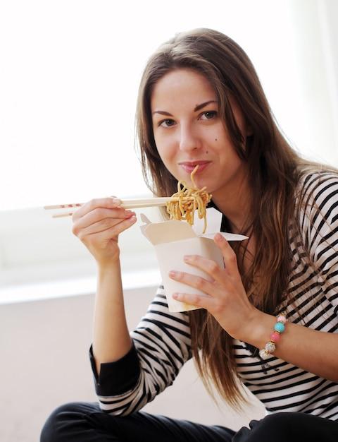 Mulher feliz comendo macarrão Foto gratuita