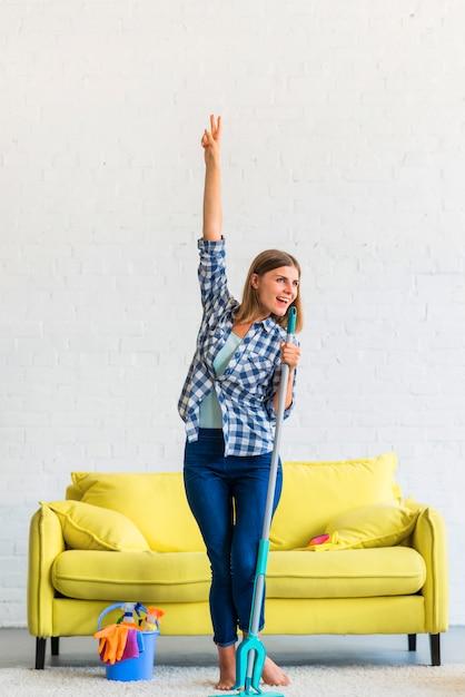 Mulher feliz dançando com esfregão em casa Foto gratuita