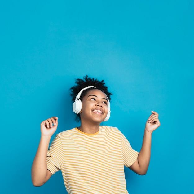 Mulher feliz dançando com fones de ouvido Foto gratuita