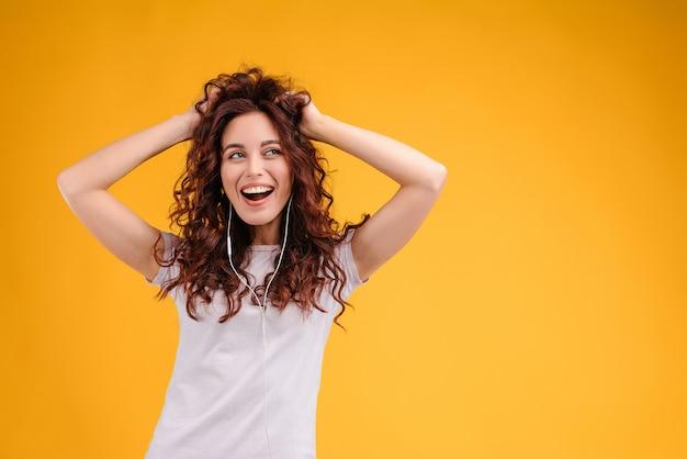 Mulher feliz dançando e ouvindo música de orelha isolada sobre o fundo amarelo Foto Premium
