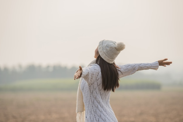 Mulher feliz desfrutando na natureza idílica, celebrando a liberdade e levantando os braços Foto gratuita