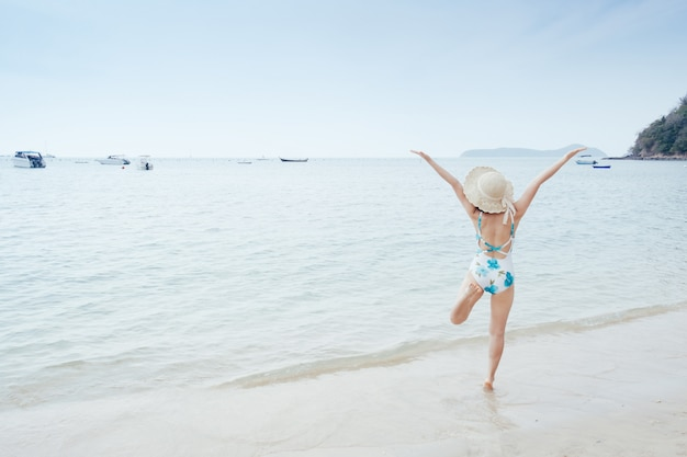 Mulher feliz do biquini no céu da praia e das nuvens. Foto Premium