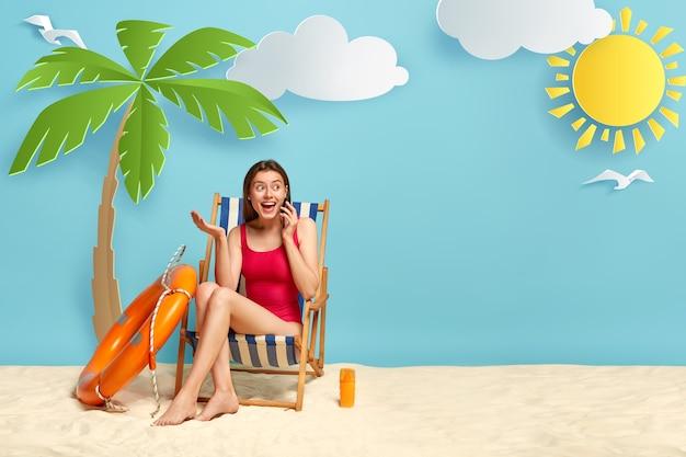 Mulher feliz e animada em trajes de banho vermelhos, relaxando em uma espreguiçadeira na praia arenosa costeira, falando no celular Foto gratuita