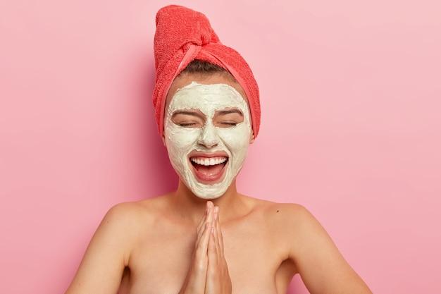 Mulher feliz e satisfeita mantém as palmas das mãos em gesto de oração, sorri amplamente, usa máscara facial para rejuvenescimento, se diverte em casa, posa nua com os ombros nus, isolada na parede rosa Foto gratuita